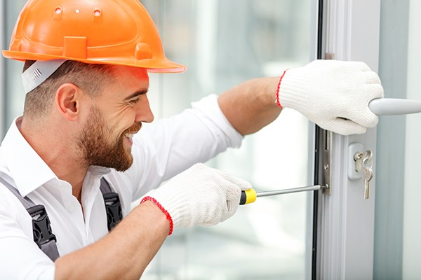 Attractive young builder is installing lock in door. He is holding a screwdriver and kneeling. The man is smiling. He is wearing a helmet