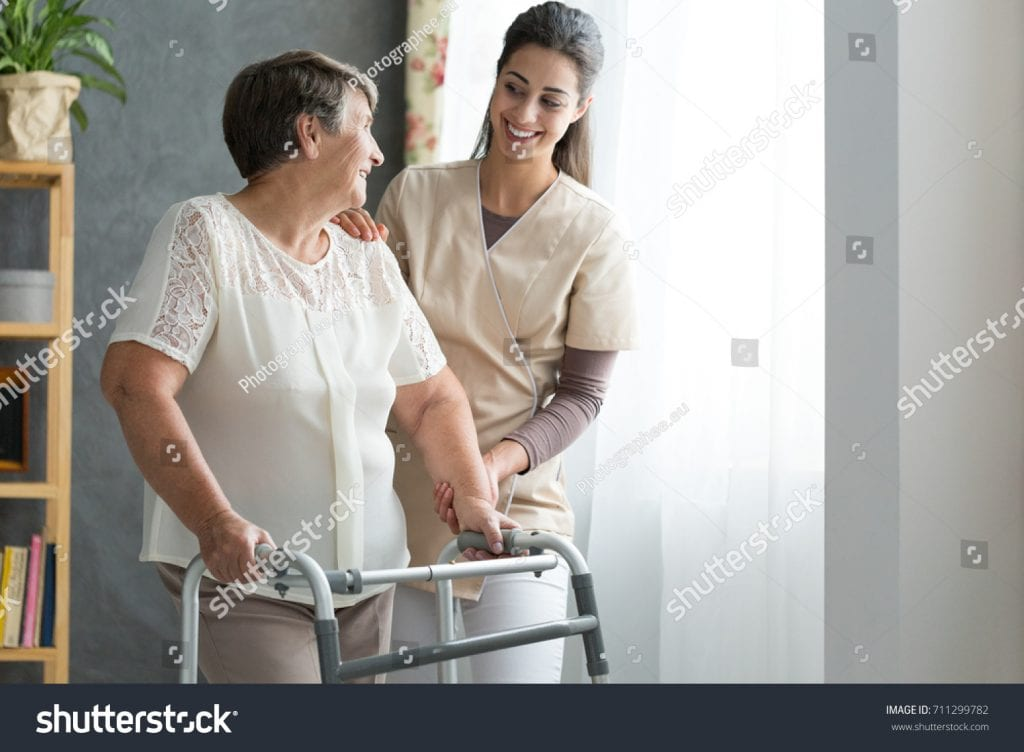 stock-photo-smiling-nurse-helping-senior-lady-to-walk-around-the-nursing-home-711299782